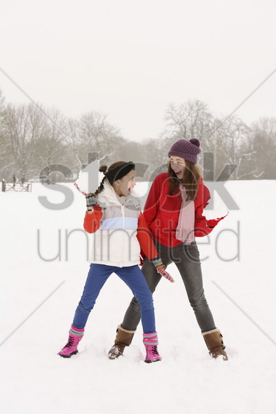 two girls playing with snowballs stock photo