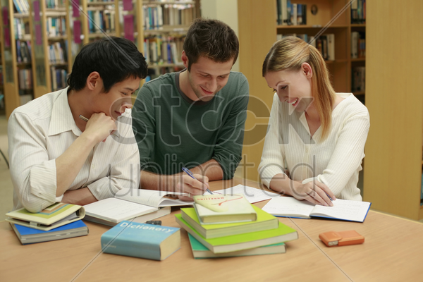 two men and a woman having discussion in the library stock photo