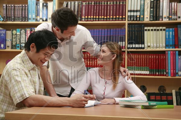 two men and a woman studying in the library stock photo
