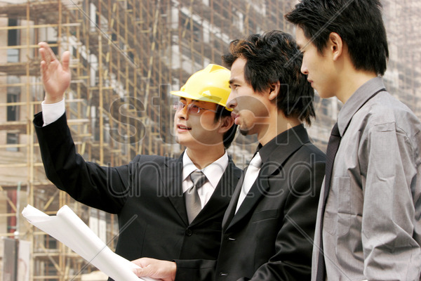 two men and an architect at the construction site stock photo