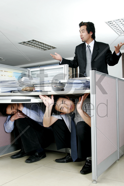 two men hiding from their manager stock photo