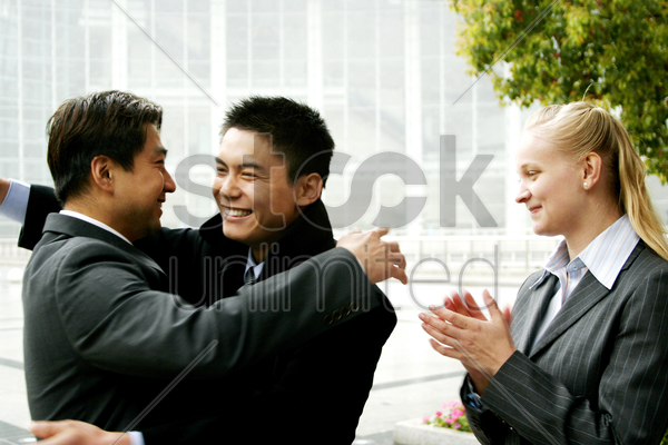 two men hugging each other while a woman clapping her hands stock photo