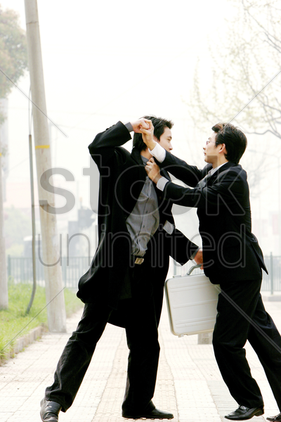 two men in business suits fighting stock photo