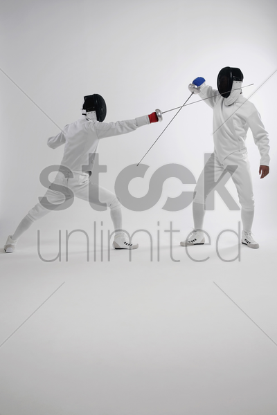 two men in fencing suits dueling stock photo