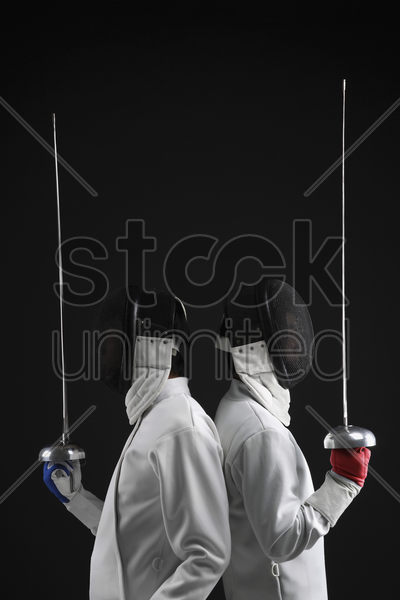 two men leaning back to back holding fencing foils stock photo