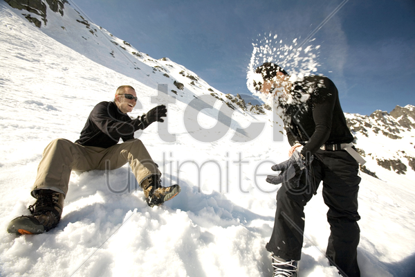 two men playing with snow stock photo