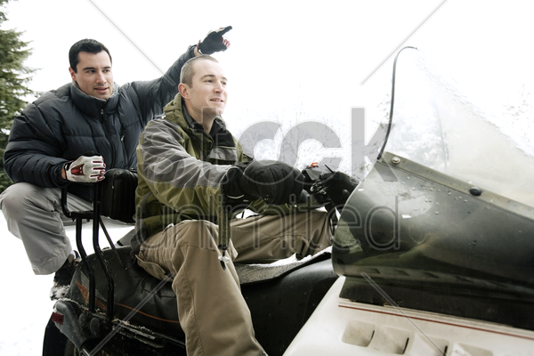 two men riding on snowmobile stock photo