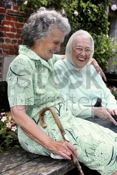 two old women having fun sitting on the bench talking stock photo