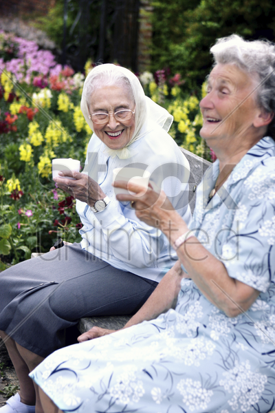 two old women sitting on a bench in the park drinking coffee stock photo