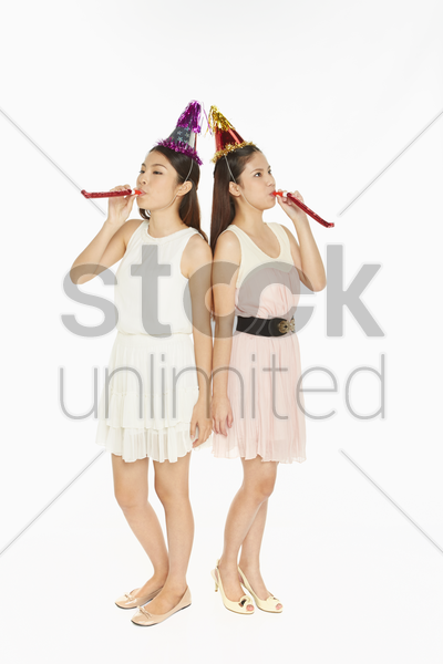 two women blowing a party horn blower stock photo