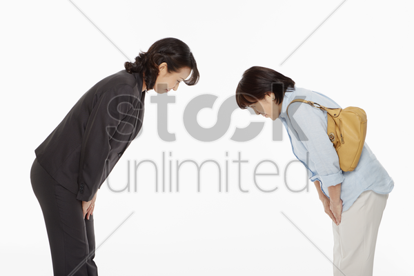 two women bowing, facing each other stock photo