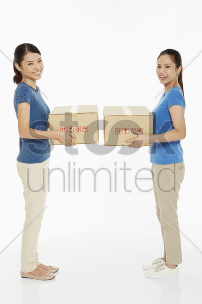 two women carrying a cardboard box each stock photo