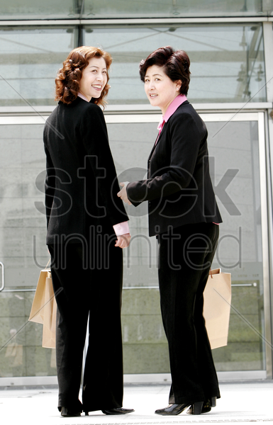 two women carrying paper bags stock photo