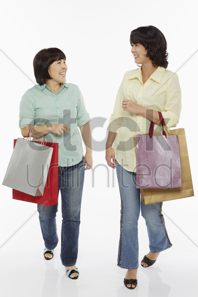 two women carrying shopping bags stock photo