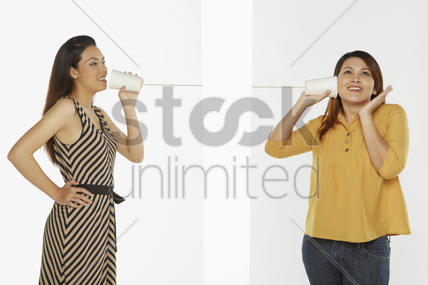 two women communicating through a paper cup phone stock photo