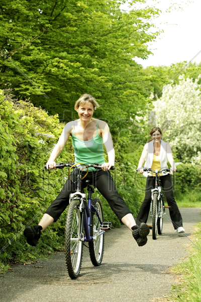 two women cycling in the park stock photo