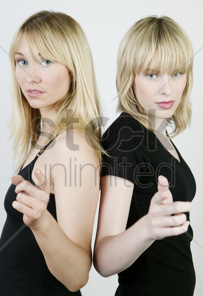 two women doing the same action stock photo