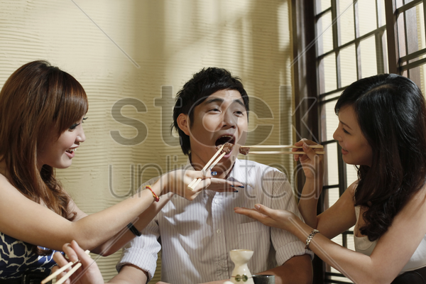 two women feeding man with grilled beef stock photo
