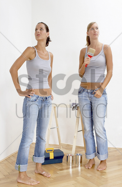 two women getting ready to paint their house stock photo