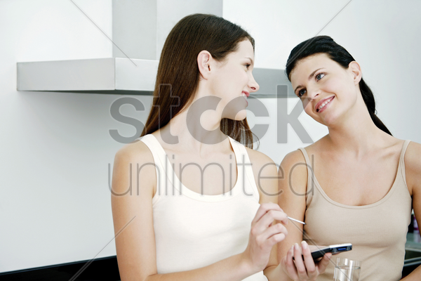two women hanging out in the kitchen stock photo