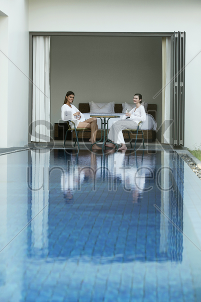 two women having a chat by the pool side stock photo