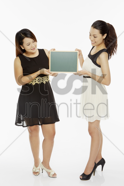 two women holding up a blank blackboard stock photo
