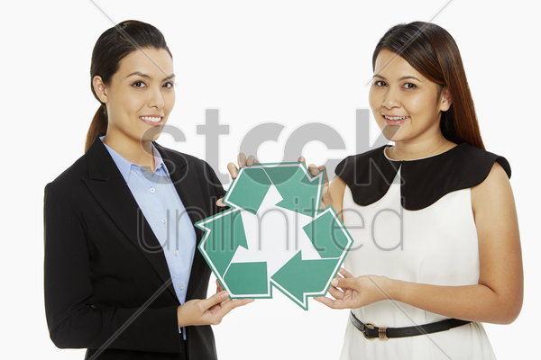 two women holding up a recycle logo stock photo