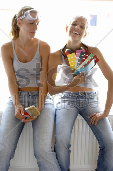 two women in jeans sitting together with one holding a brush while the other holding colour cards stock photo
