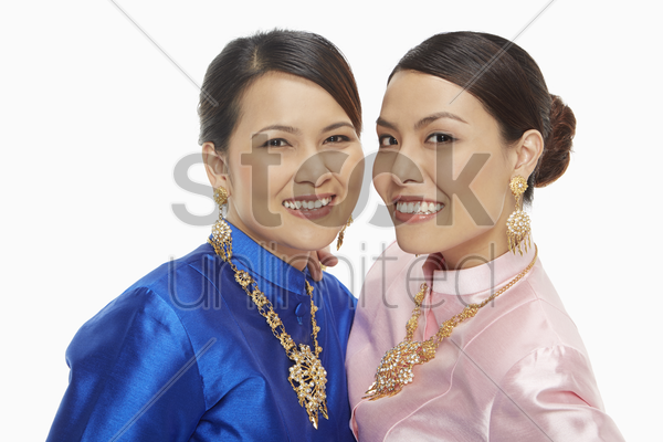two women in traditional clothing smiling at the camera stock photo