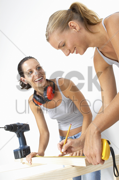 two women laughing as they were measuring a wood stock photo