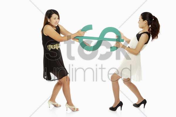 two women pulling a dollar sign stock photo