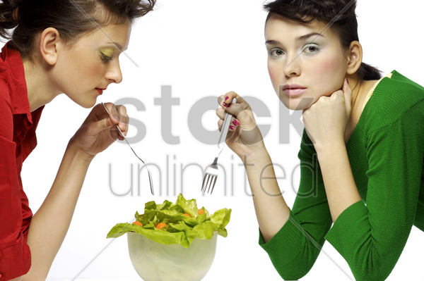 two women sharing a bowl of salad stock photo