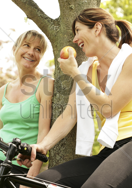 two women talking while sitting on bicycles stock photo