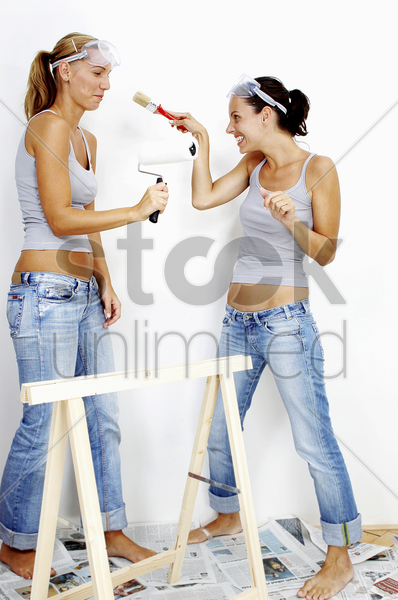 two women with goggles with one holding a roller while the other holding a brush stock photo