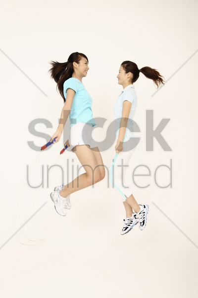 two young women playing with skipping rope stock photo