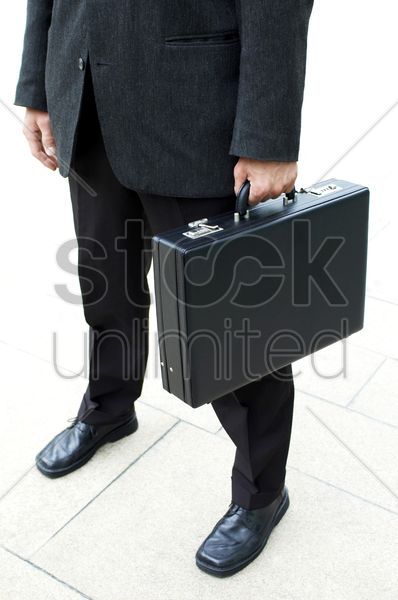 waist down shot of a businessman carrying a briefcase stock photo