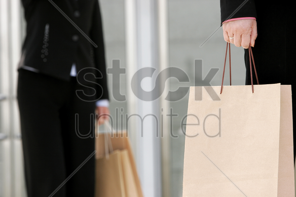 waist down shot of two business women carrying paper bags stock photo