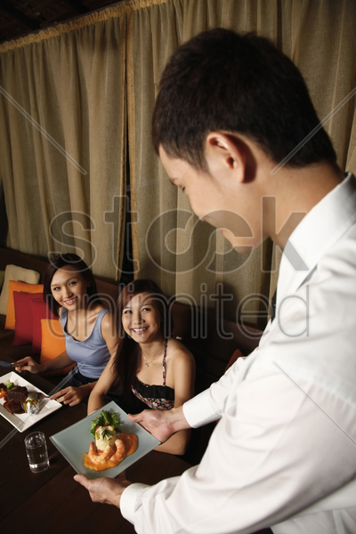 waiter serving food to women stock photo