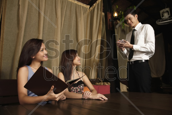waiter taking orders from women stock photo