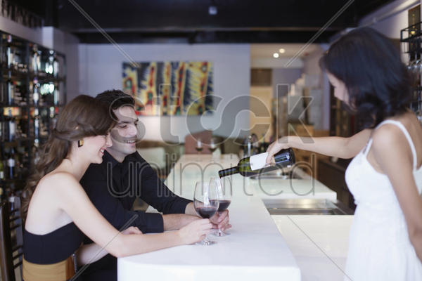 waitress pouring wine for man and woman at the bar stock photo