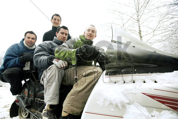 winter sport players posing on snowmobile stock photo