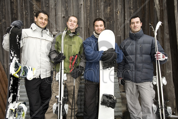 winter sport players with their skis and snowboards stock photo