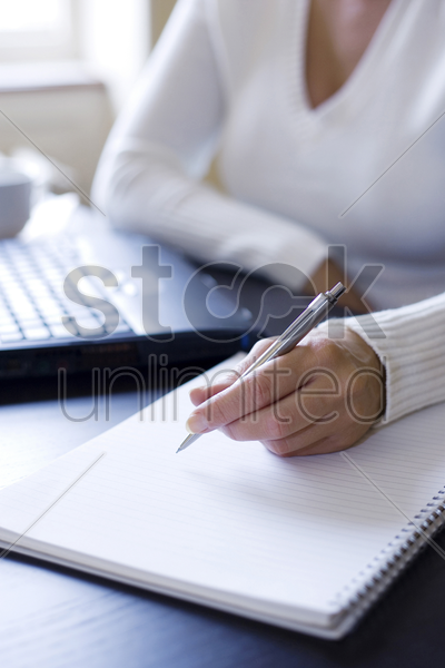 woman about to write on a notebook stock photo