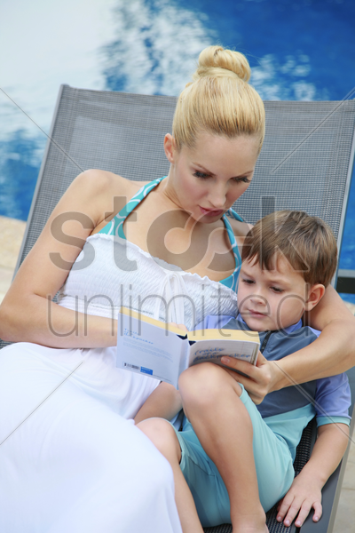 woman and boy sitting on lounge chair reading a book together stock photo