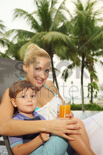 woman and boy sitting on lounge chair smiling stock photo