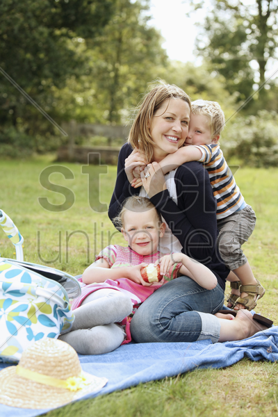woman and children having a picnic at the park stock photo