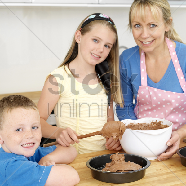 woman and girl baking in the kitchen, boy smiling at the camera stock photo