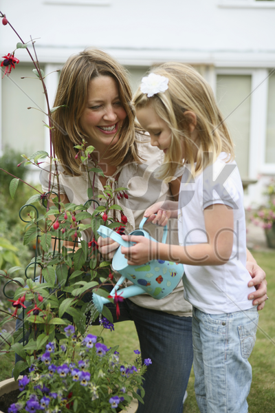 woman and girl watering plants stock photo