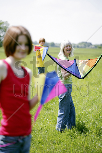 woman and her children holding kites stock photo