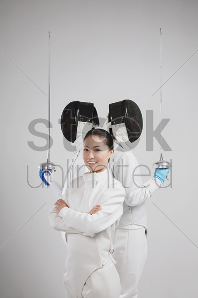 woman and two men in fencing suits posing for the camera stock photo